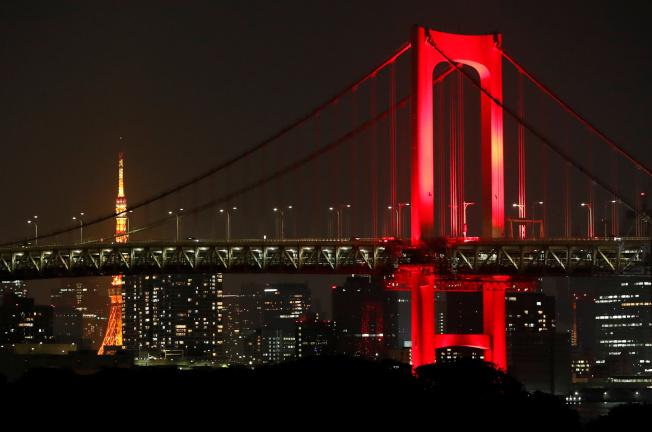 「東京警報」發布後,2日晚東京臨海地區的彩虹大橋打上紅色燈光,提醒市民提高警覺防疫。(路透)