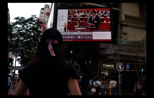 圖為5月28日下午,香港民眾在銅鑼灣街頭通過大螢幕觀看中共全國人大表決推過香港國安立法的決定。(中新社)
