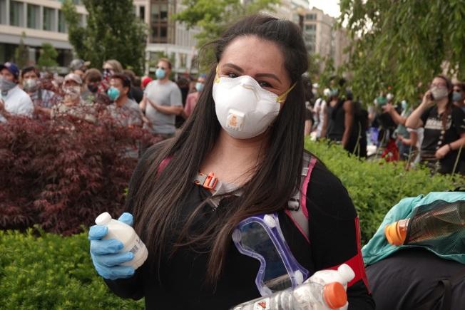 Carolina在物資供應站協助免費提供水跟食物給參加抗議活動的民眾。華盛頓記者張文馨/攝影