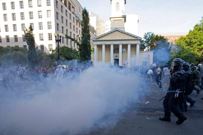 川普總統1日傍晚在華府即將宵禁前安排探視被燒損的歷史古蹟聖約翰教會,下令軍警強行開道,用催淚彈驅散示威者,引發爭議批評。圖為軍警1日用煙霚催淚彈驅散在教會前的示威者。(美聯社)
