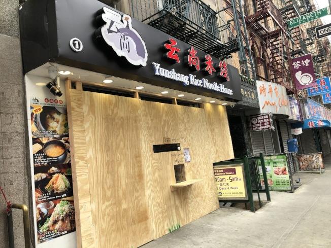 餐館釘上木板後,在門口留一個取餐洞口。(讀者提供)