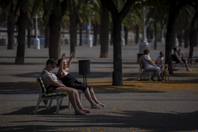 3日在西班牙巴塞隆納,人們在公園長凳上曬太陽。(美聯社)