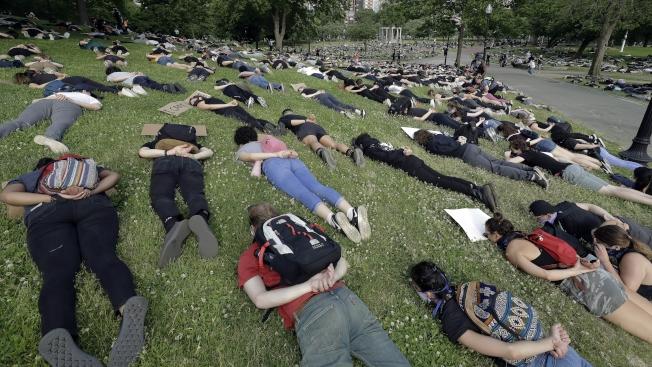 示威者喊口號、單膝脆地或躺地裝死8分46秒,哀悼被明尼蘇達警察壓頸致死的非裔弗洛德。(美聯社)