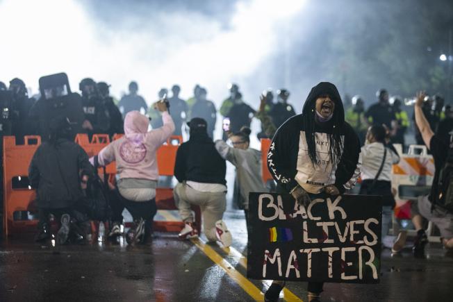 大群民眾聚集在布洛克頓市警察總部外,有人向警察和國民兵扔瓶子、射煙火。(美聯社)