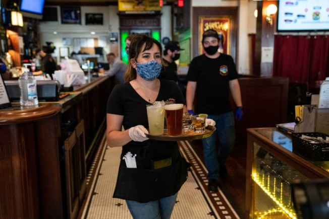 儘管加州病例數持續增加,但重啟經濟的計畫依舊持續。圖為洛杉磯市San Pedro Brewing Company一位女侍戴著口罩,為客人端上啤酒。(洛杉磯時報)