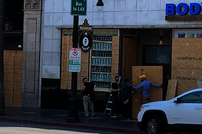 商家用木板加固門窗防盜。(記者陳開/攝影)
