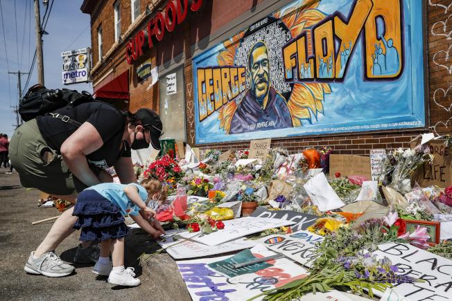 圖為明尼蘇達州居民拿著鮮花到非裔男子佛洛伊德遭白警致死地點悼念。(美聯社)