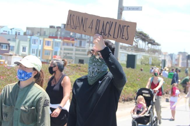 遊行中大部分人都有戴口罩。(記者李晗╱攝影)