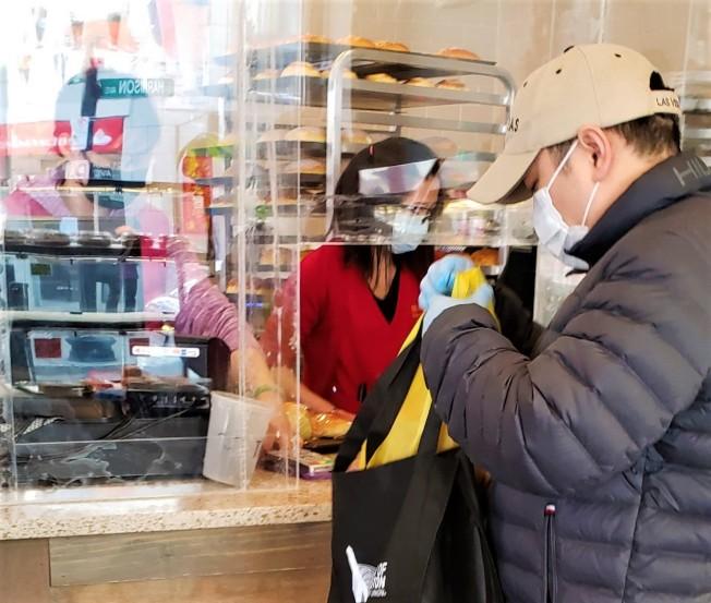 一家波士頓華埠烘焙店在收銀台前架置隔離員工與顧客的透明塑膠板,以加強防疫安全。(記者唐嘉麗/攝影)
