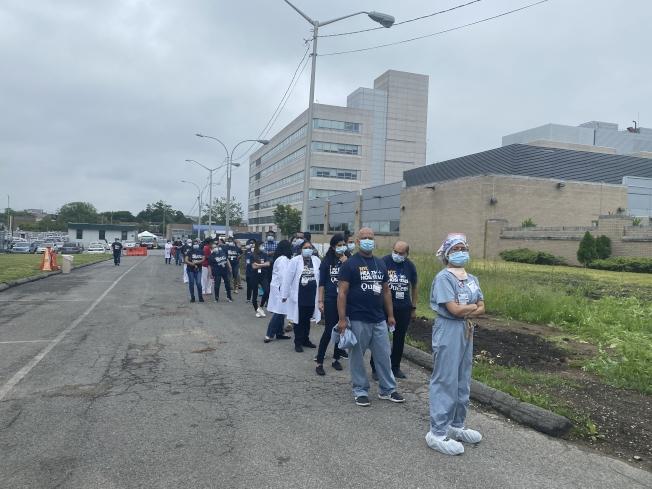 醫護人員排著長隊等待領取餐食與口罩。(記者牟蘭/攝影)