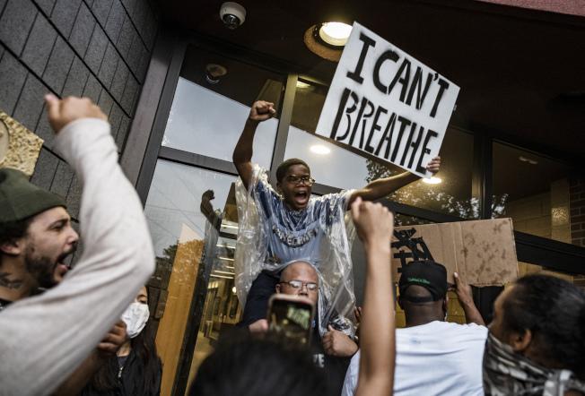 美國5月黑人失業率攀抵逾十年來最高,圖為示威者手舉「我無法呼吸」標語。(美聯社)