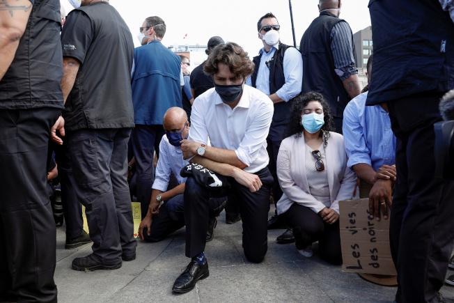 加拿大總理杜魯多5日在渥太華國會山莊的「反種族主義」活動中,帶著黑色口罩、左膝跪在地上表示支持。(路透)