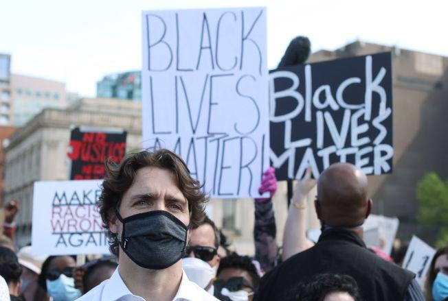 加拿大總理杜魯多5日在渥太華國會山莊的「反種族主義」活動中,帶著黑色口罩、單膝跪在地上表示支持。(Getty  Images)
