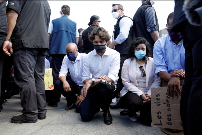 加拿大總理杜魯多5日在渥太華國會山莊的「反種族主義」活動中,帶著黑色口罩、右膝跪在地上表示支持。(路透)