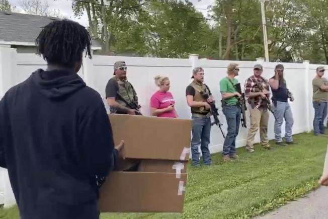 印第安納州示威者1日在鄉村冠點市和平遊行,譴責種族歧視與警察殺害非裔;現場有21名路人沿道站立觀看,其中八名白人手持槍械。(美聯社)