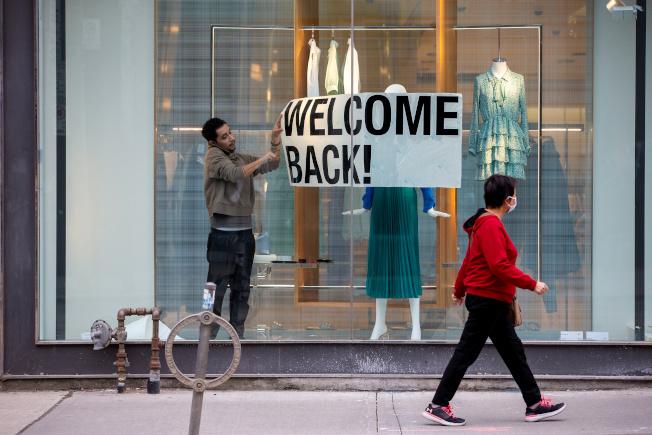 面對復工在即,有人擔心回職場感染新冠肺炎,有人擔心繼續待在家會失去工作,勞工陷入兩難。圖為一家服飾店員工正在櫥窗布置「歡迎回來」的廣告招牌。(路透)