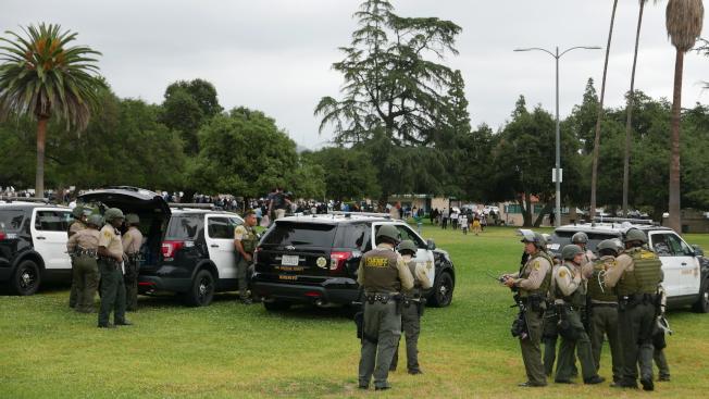在草坪的另一端,數十輛縣警警車停在現場,數十警員們都全副武裝,遠遠看著遠處的集會現場。(記者李雪/攝影)