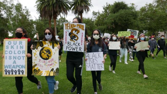 在遊行隊伍的最前端,一名華裔女學生舉著標語,寫著「黃禍支持黑人的生命」(Yellow Peril for Black Lives)。(記者李雪/攝影)