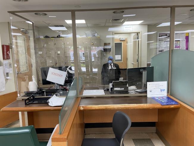 在候診大廳,醫務人員在新建的塑料隔板後篩查評估病患。(記者鄭怡嫣/攝影)