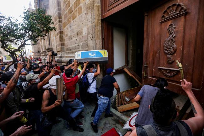 示威者4日在瓜達拉哈拉示威,有人破壞政府建築物及燒毁數輛警車。(路透)