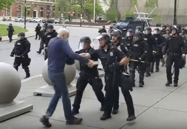 75歲和平示威者被兩名警員推倒在地。(美聯社)