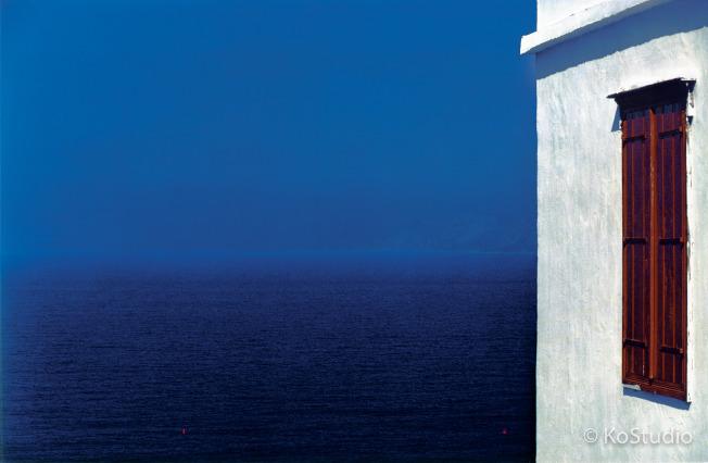 被譽為「台灣現代攝影第一人」的攝影家柯錫杰5日晚間辭世,他在西元1979年於希臘拍下經典作品「等待維納斯」,畫面中的藍海、白牆與紅窗,整體構圖宛如一幅畫。(中央社/柯錫杰工作室提供)