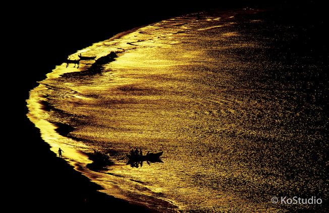 攝影家柯錫杰5日晚間辭世,他在西元1988年於中國福建海邊所拍作品「金海」為一經典之作,在黑與金交織的畫面中,隱約可見幾艘船與漁夫,為照片賦予不同的生命力。(中央社/柯錫杰工作室提供)