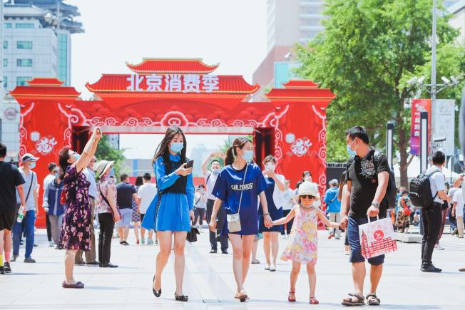 北京降低疫情防範級別,昨天在各區啟動消費季,圖為王府井大街上的遊客。(中新社)