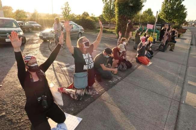 示威者跪在地上,抗议警察开枪击毙蒙特洛沙时,他是双膝跪在警察面前的。(取自推特)