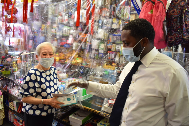 多瑞斯(右)送口罩給華埠商家。(記者顏嘉瑩/攝影)