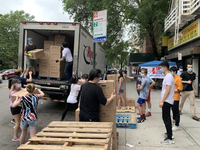 配送過程仰賴志工將食物一箱一箱搬上卡車。(孔振成提供)