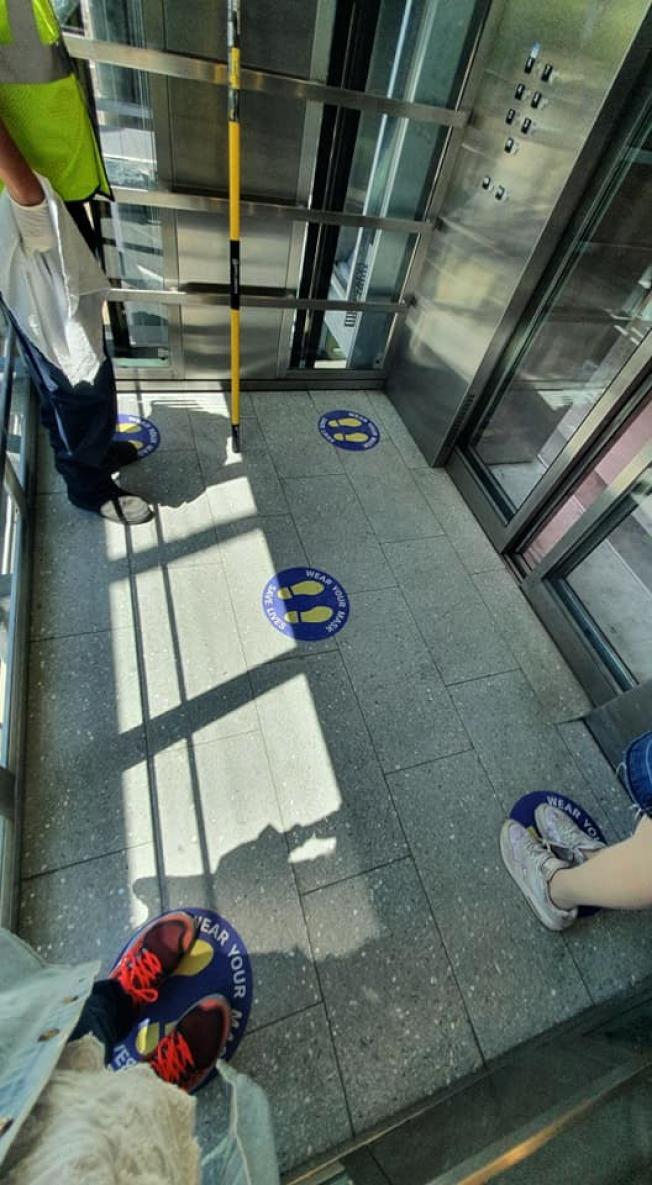 為應對新冠疫情,拉瓜地亞機場電梯裡提醒保持社交距離的貼紙,最多只能五人搭乘。(記者王彩鸝/攝影)