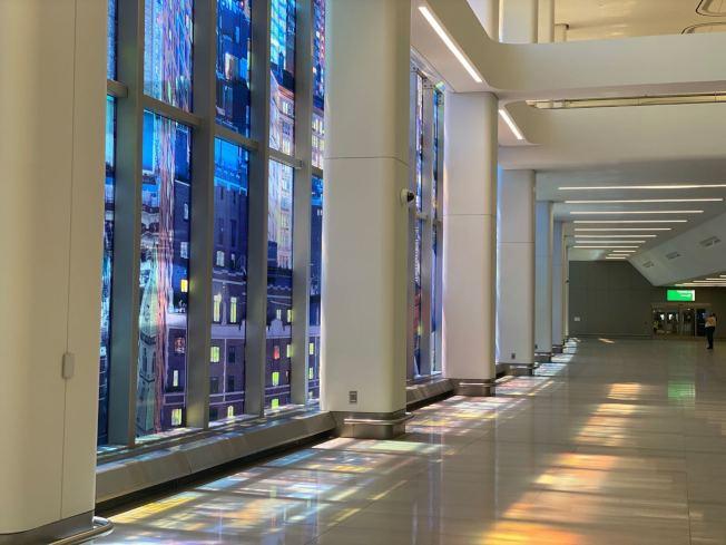 新候機大廳連結停車場與B航站樓的落地玻璃則貼有藍色為主的彩色貼紙也成為一大亮點,在陽光照射下在貼紙在磁磚上反射出彩色倒影。(記者牟蘭/攝影)