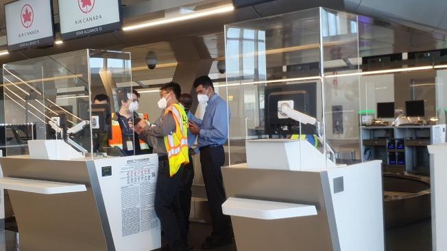 拉瓜地亞機場地勤工作人員設有亞克力的擋板,避免新冠病毒通過飛沫傳播。(記者王彩鸝/攝影)