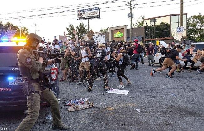 亚城白人警员12日晚涉嫌过度用武,枪杀拒捕的非裔布鲁克斯,立即引发亚城非裔社区的愤怒不平。图为事发现场附近的温蒂速食店13日民众愤怒抗议。左为警方持枪紧张看守现场。(美联社)