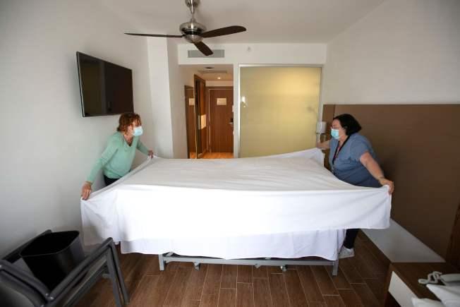 各大旅館業者通常要以價位或特色競爭,現在還得比較清潔程度;從前台工作人員戴口罩、到關閉自助餐區,面對新冠疫情,業者紛紛進行顯而易見的改革。圖為清潔人員整理旅館房間。(Getty Images)