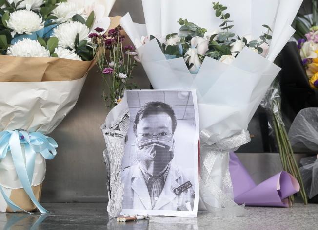 今年2月8日武漢民眾在武漢市中心醫院附近一處臨時處所放置李文亮的遺照悼念他。(歐新社)