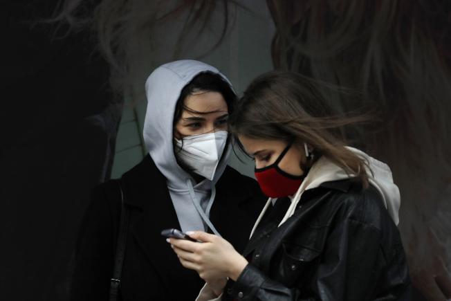 圖為在紐約時報廣場,民眾戴著口罩。美聯社
