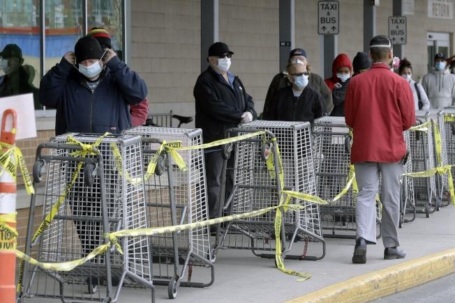 圖為戴著口罩的消費者保持社交距離,在麻州Chelsea一家超市外排隊等候入內。(美聯社)