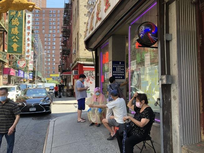 理髮店前坐著不少等候理髮的客人,李太太(坐者左一)自備雨衣和毛巾燙髮。(記者顏嘉瑩/攝影)