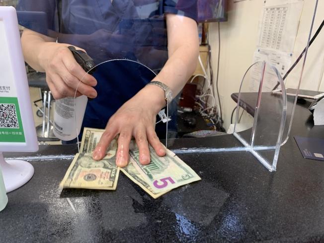 華人理髮業者注重清潔與消毒,找客人錢之前會噴酒精消毒。(記者賴蕙榆/攝影)