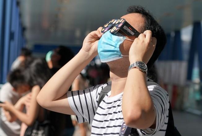 圖為市民戴上特質眼鏡觀看日偏食。(中新社)