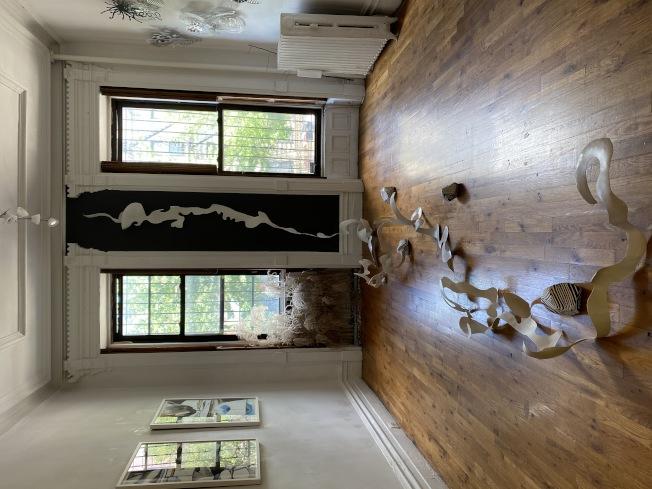展覽的中心裝置是一條名為「曲水」的河,由白色鋁板構成,彎曲成水花的景象。(記者金春香 / 攝影)