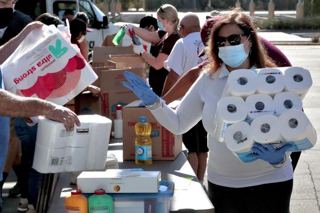 佛州疫情失控,州長仍不准各郡下令強制戴口罩。圖為志願者在坦帕市戴口罩協助發送物資。(美聯社)