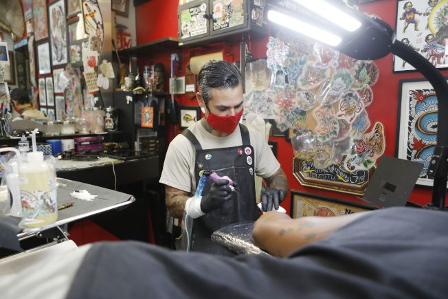 佛州疫情失控,州長仍不准各郡下令強制戴口罩。圖為坦帕市刺青店的工作人員市戴口罩工作。(Getty Images)