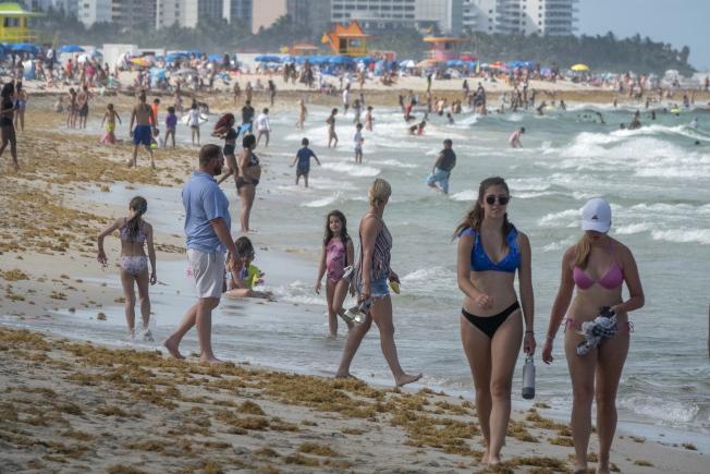 佛州過去24小時新增9585人確診感染,連續第二天改寫單日新高紀錄。圖為邁阿密海灘上仍湧進戲水的人潮。(歐新社)