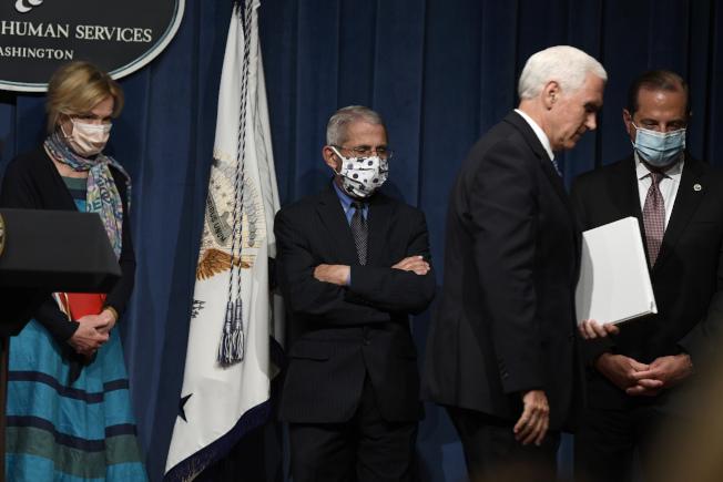 是否要強制戴口罩,已成為敏感政治議題。川普總統的白宮防疫小組成員都戴口罩出席記者會。唯獨川普總統與副總統潘斯(前右)至今不戴口罩。左為防疫協調專員柏克斯、公衛專家佛奇(中)、衛生部長阿查爾等出席26日白宮記者會都戴了口罩。(Getty Images)