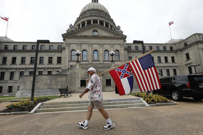 密西西比州議會28日通過表決將全美最後一面印有邦聯標誌,帶有種族歧視意味的州旗移除。圖為一名支持州旗的民眾在州議會外抗議。(美聯社)