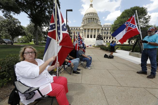 密西西比州議會28日通過表決將全美最後一面印有邦聯標誌,帶有種族歧視意味的州旗移除。圖為少數支持州旗的民眾在州議會外抗議。(美聯社)