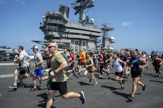 艾森豪號航空母艦官兵在飛行甲板上跑步健身。(美聯社)